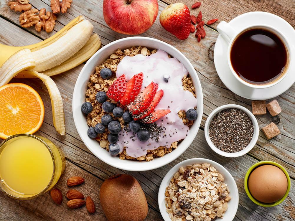 Tisch voller gesunder Lebensmittel wie Erdbeeren, Banane, Müsli und Nüsse