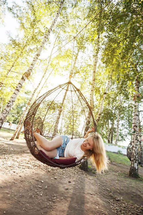 Frau lachend auf Schaukel im Garten befestigt zwischen zwei Bäumen