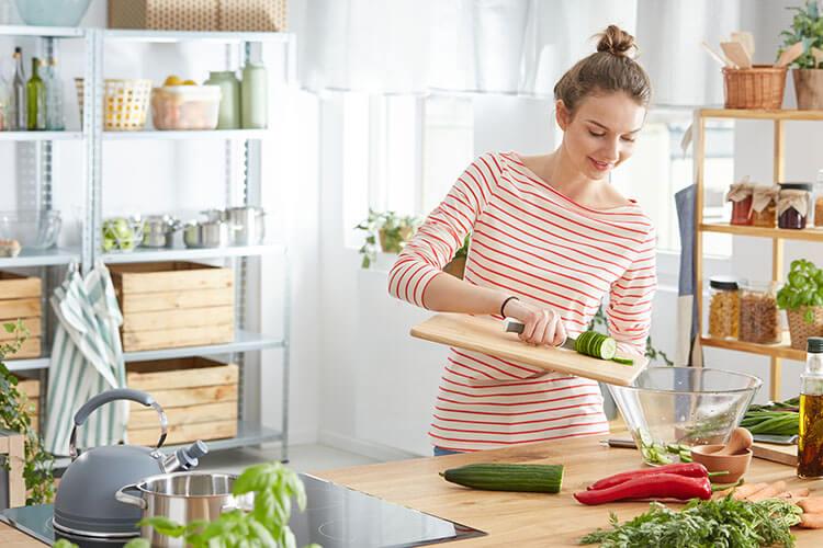 Junge Frau bereitet in Küche gesundes Essen aus Obst und Gemüse vor
