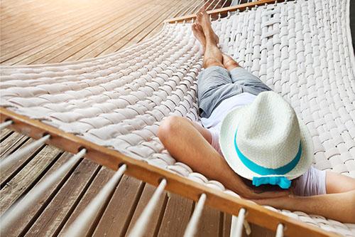 Mann mit Hut enstpannt oder schläft in Hängematte