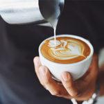 Mann gießt Milch in Kaffee und erzeugt dadurch eine Blume auf dem Kaffee-Schaum