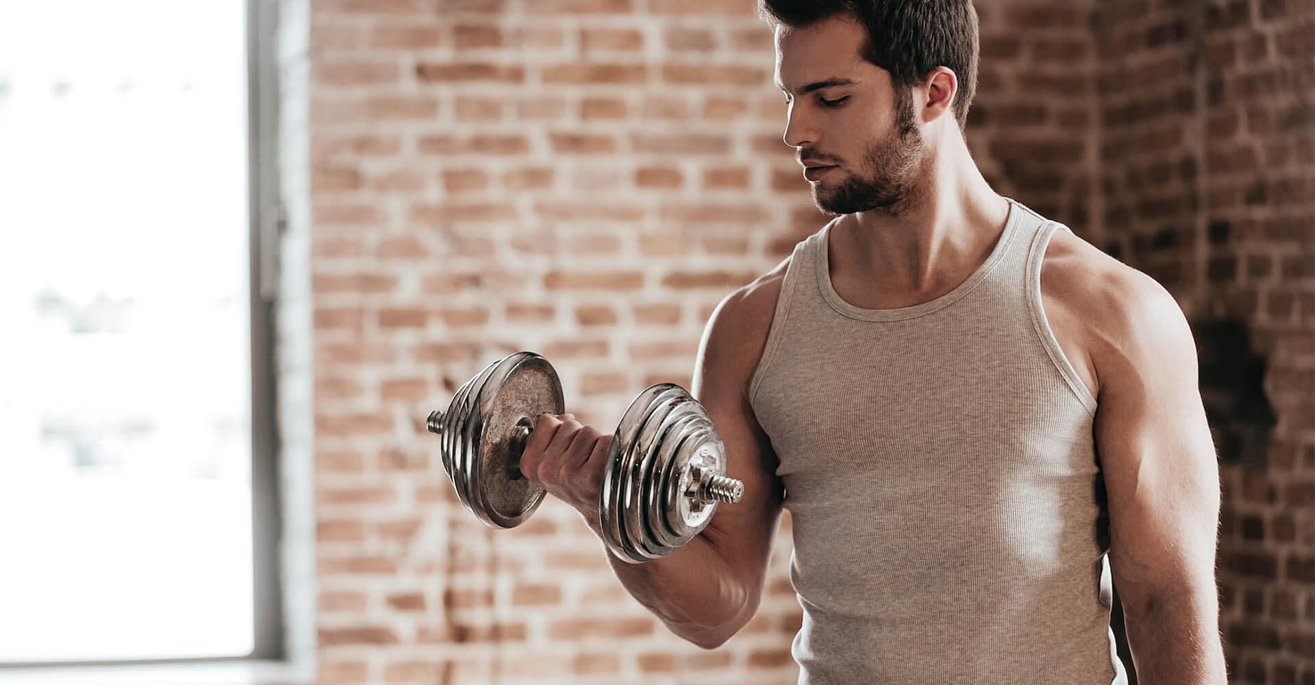 Mann führt zuhause mit Hanteln Kraftsport Übungen durch.