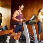 Mann läuft auf Laufband, während Frau auf Crosstrainer trainiert