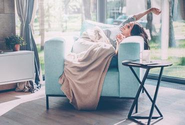 Frau streckt sich freudestrahlend und ausgeschlafen in Sessel im lichtdurchflutetem Wohnzimmer