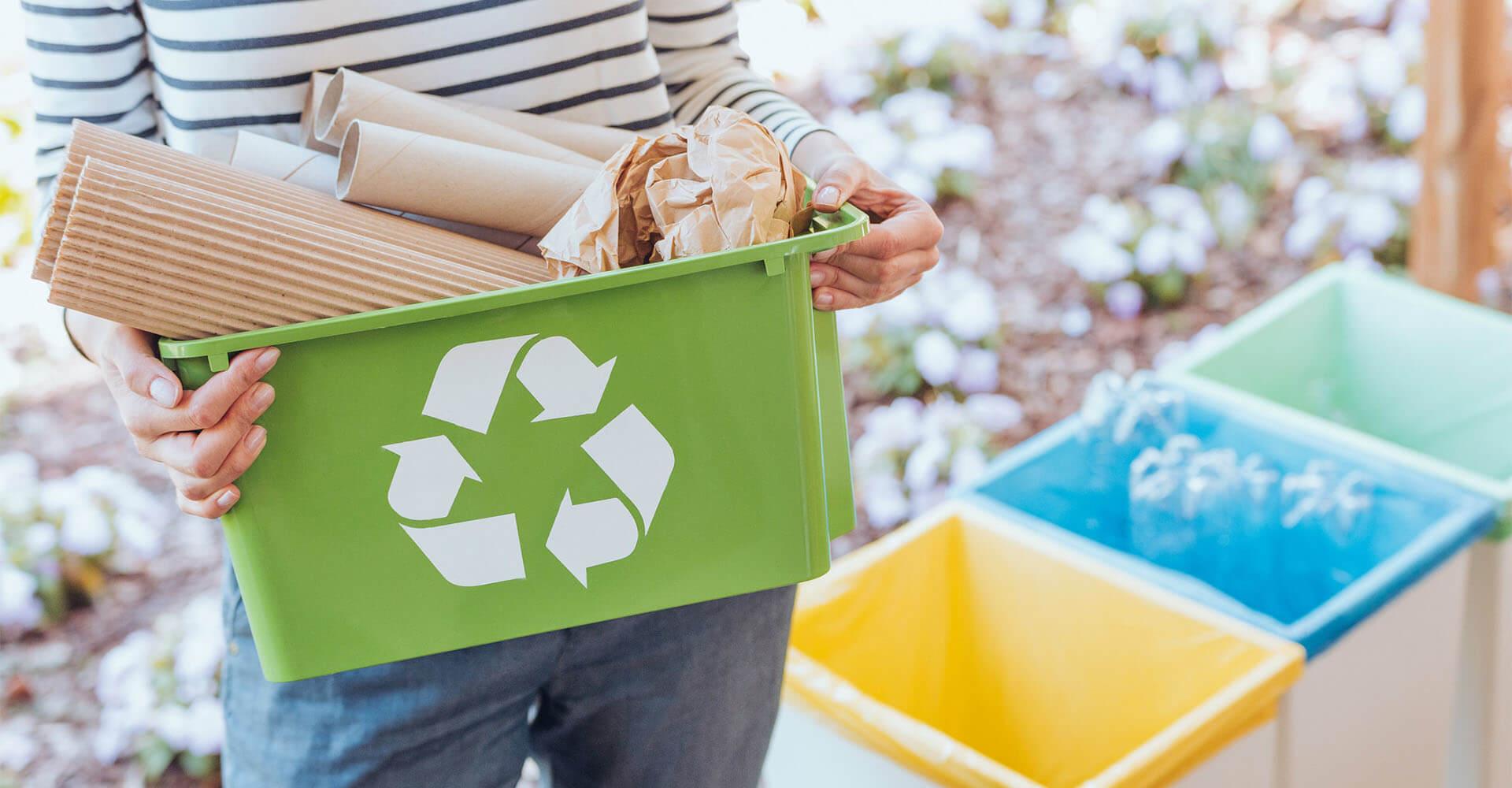 Frau bringt Müll zu Mülleimer vor der Haus