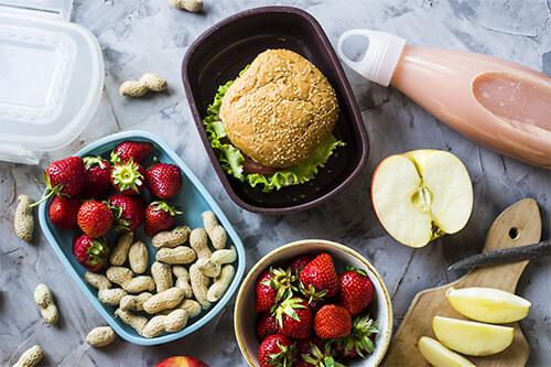 Meal Prep Frühstück mit Erdbeeren, Erdnüssen, Äpfeln und einem Burger