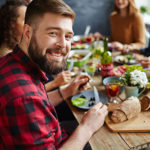 Mann sitzt lächelnd am Mittagstisch mit Freunden und isst