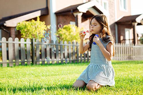 Mädchen spielt im Garten mit Seifenblasen