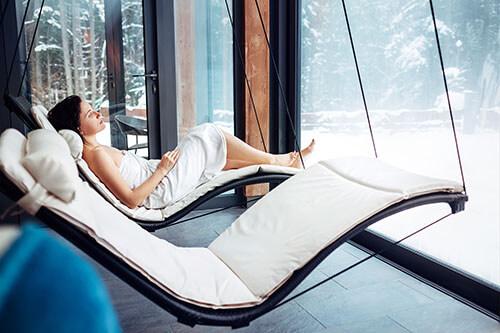 Frau entspannt in Handtuch nach Saunagang auf einer Liege