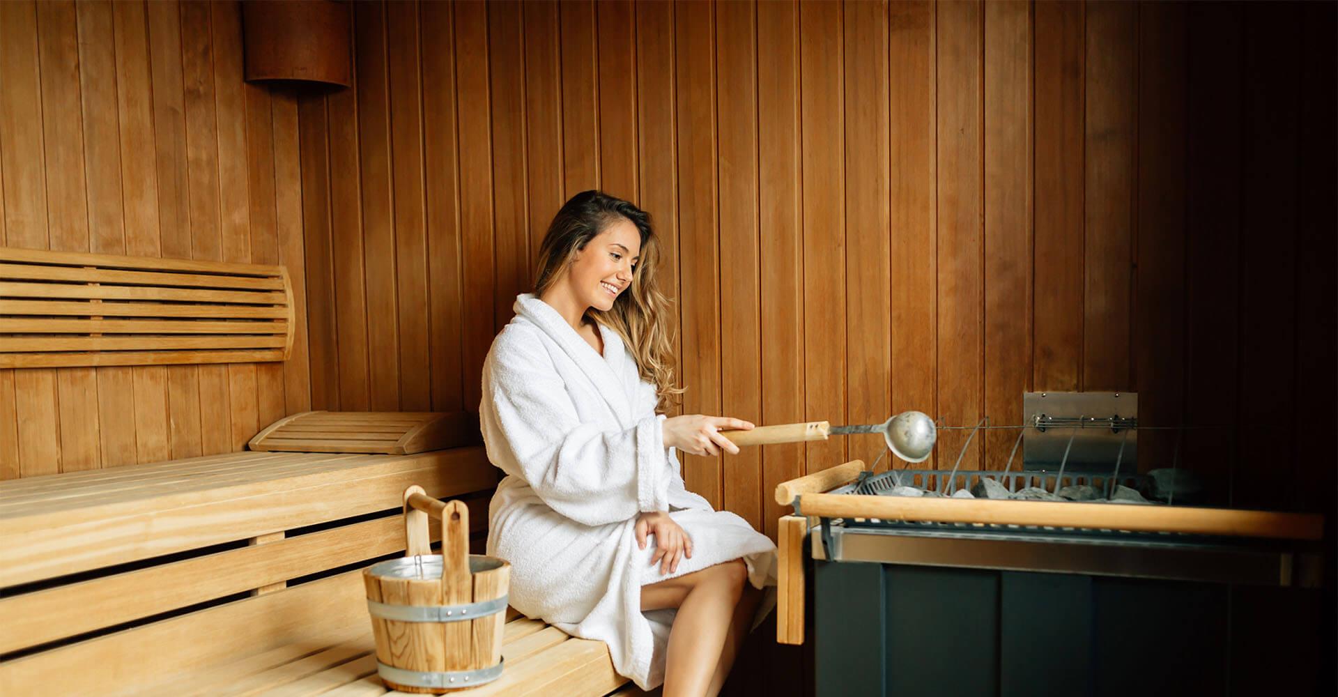 Frau sitzt mit Bademantel in Sauna und macht einen Aufguss, um in der Sauna abzunehmen