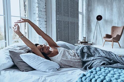 Frau wacht morgens ausgeschlafen und entspannt auf
