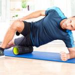 Mann trainiert zuhause auf Isomatte und Faszienrolle