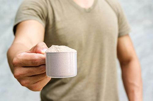 Muskulöser Mann hält Messbecher voll mit Eiweißpulver vor sich