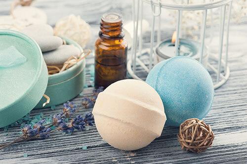 Mehrere Wellness-Utensilien wie Badekugeln, Öl und Kerzen