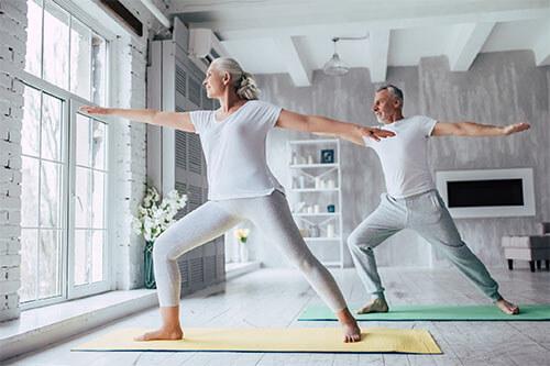 Älteres Senioren-Paar macht Yoga-Übungen zuhause