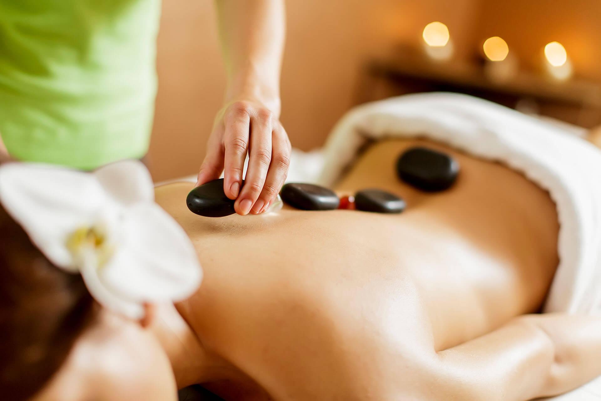 Frau bekommt Massage zuhause mit Steinen