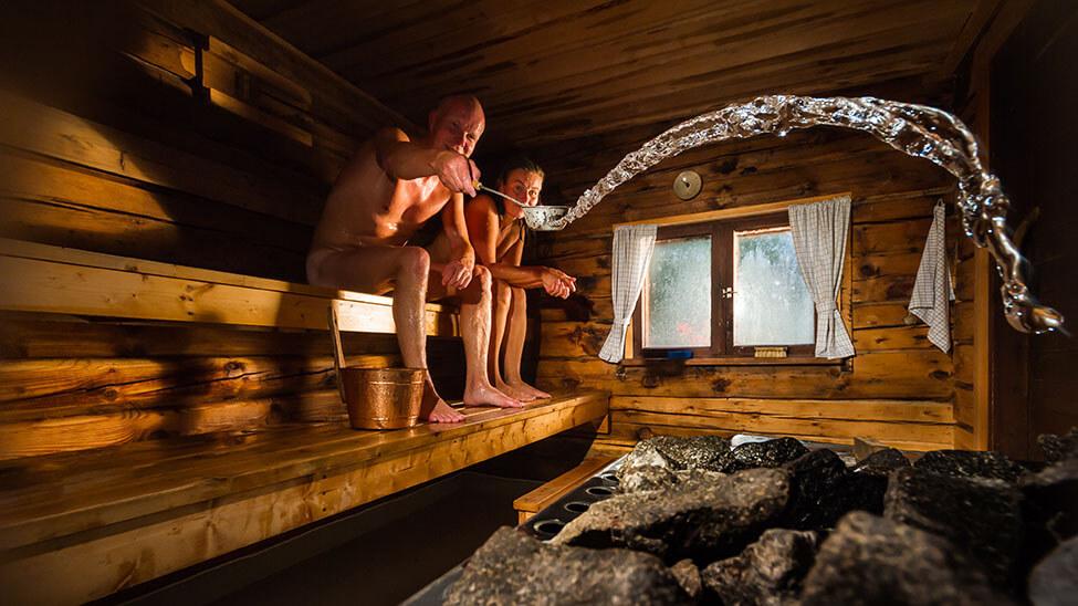 Ein Paar in der Sauna, das entspannt mit einer Kelle Wasser auf die Sauna-Kohle schüttet