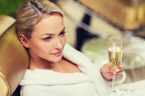 Schöne Frau entspannt nach Sauna mit Champagner in Hand