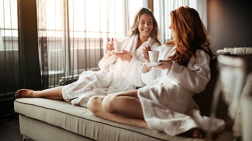 2 Frauen entspannen nach Gang in die Sauna im Bademantel auf Sofa mit Kaffee in der Hand