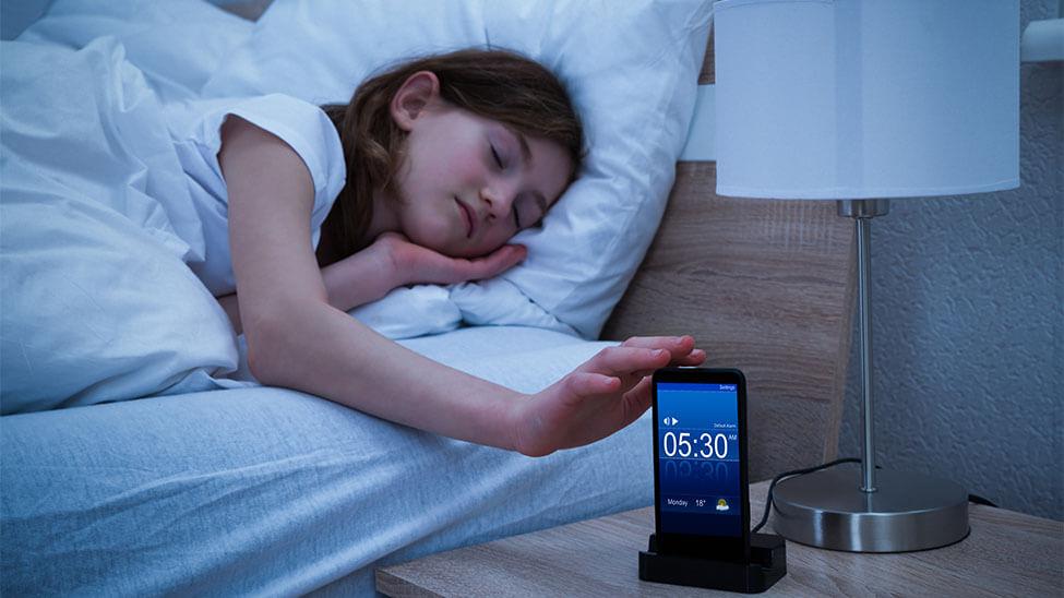 Schlafendes Mädchen neben Wecker