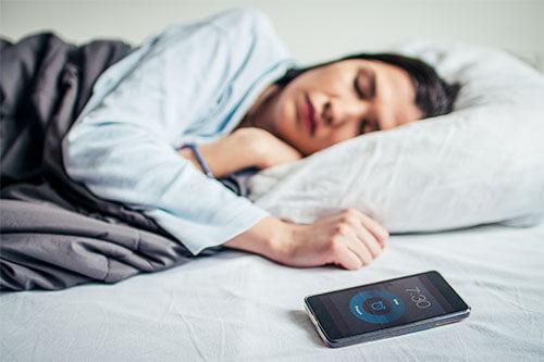 Frau schläft im Bett mit Schlafphasenwecker und per Bluetooth verbundenen Smartphone
