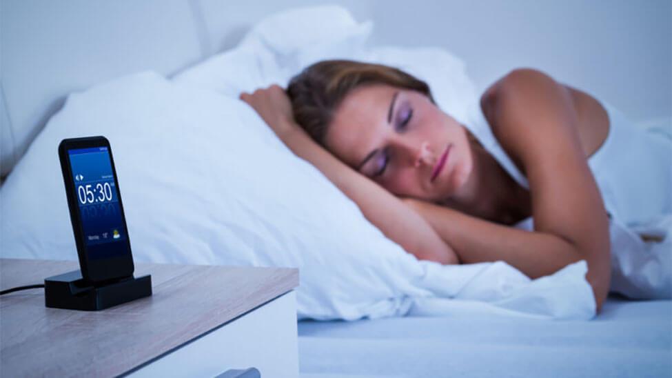 Smartphone neben schlafender Frau