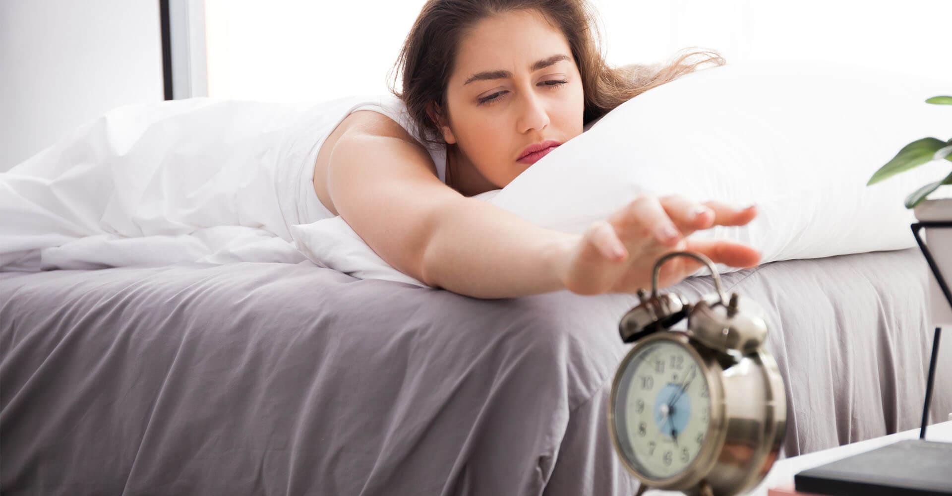 Frau liegt im Bett und greift nach Wecker