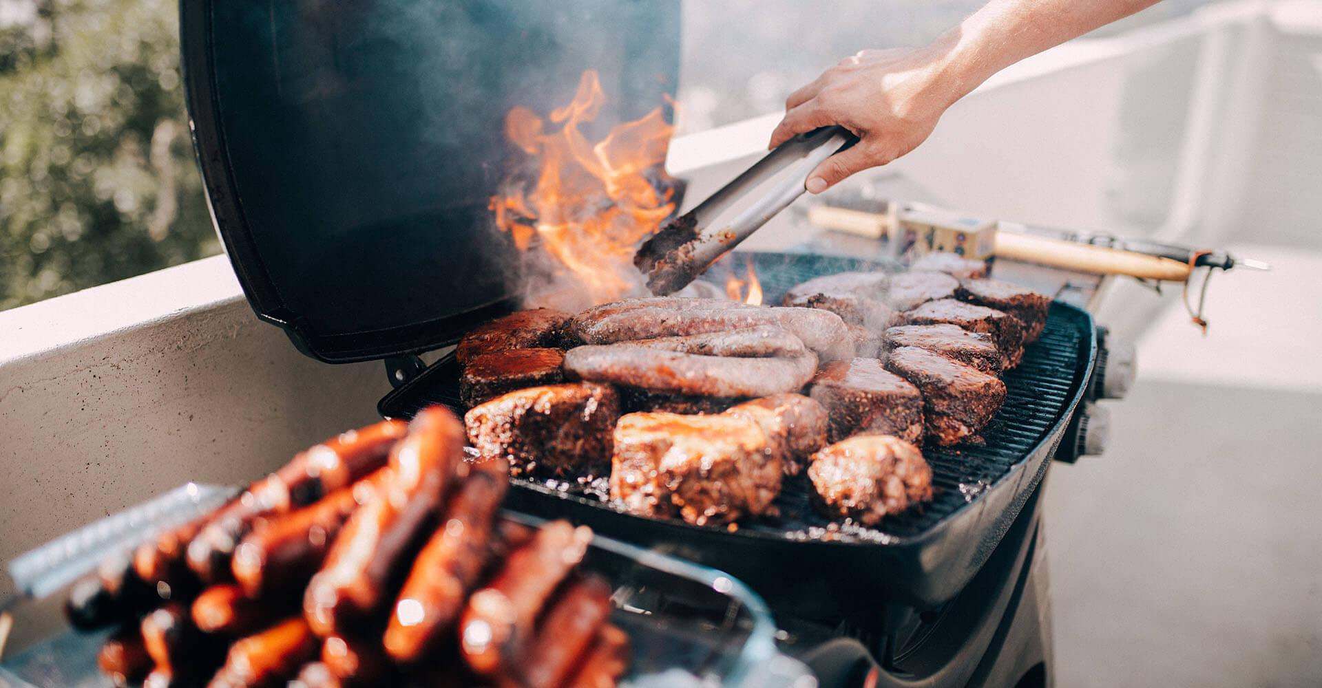 Auf einem Grill werden Steaks und Wüstchen gebraten