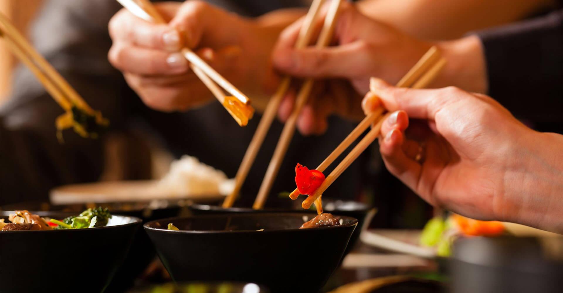 Leute essen Gerichte aus Asiatisches Küche mit Stäbchen