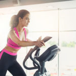 Frau trainiert auf Crosstrainer zuhause