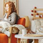 Frau liest in Leseecke auf gemütlichem Sessel ein Buch