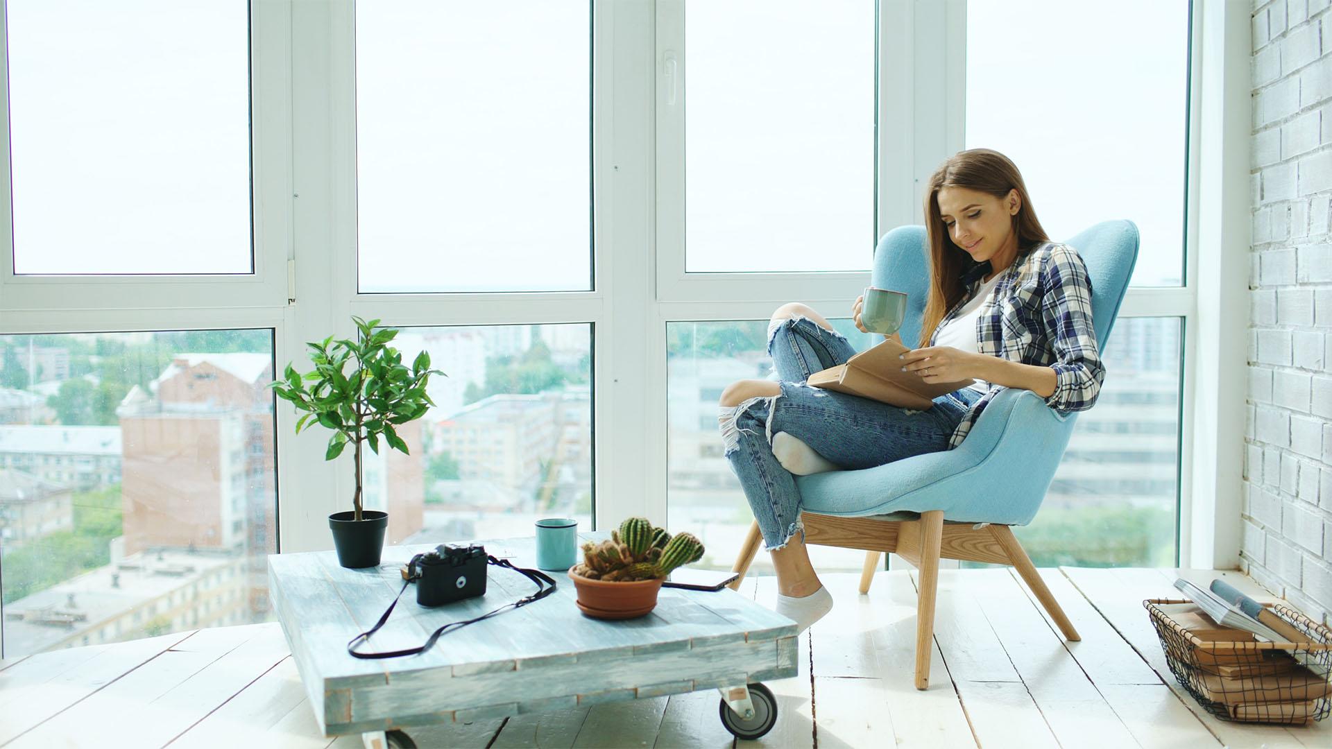 Frau liest in Lesesessel ein Buch