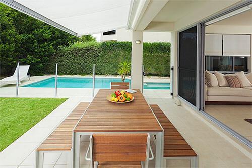 Markise auf Terrasse mit offenem Wohnzimmer und Pool im Hintergrund