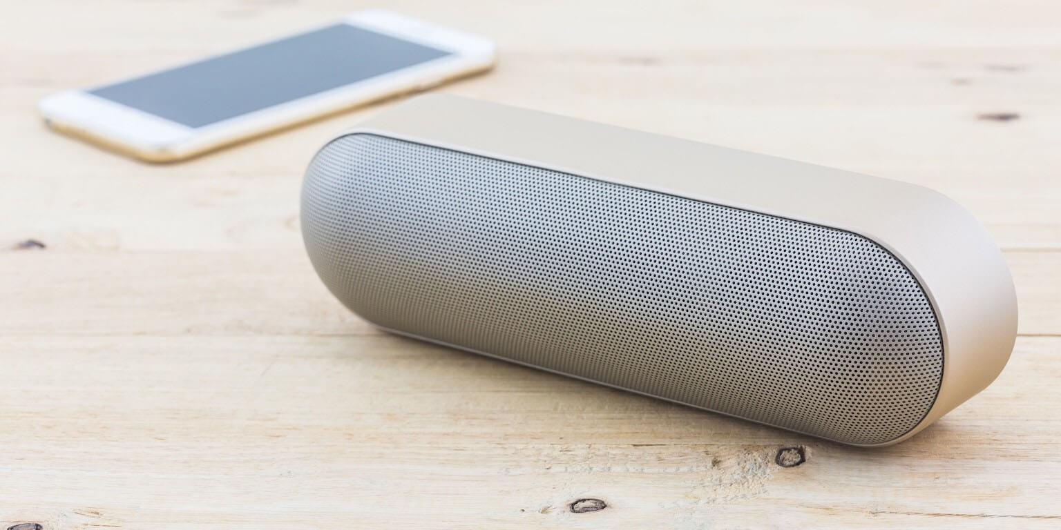 Helle Bluetooth Lautsprecher mit weißem Smartphone