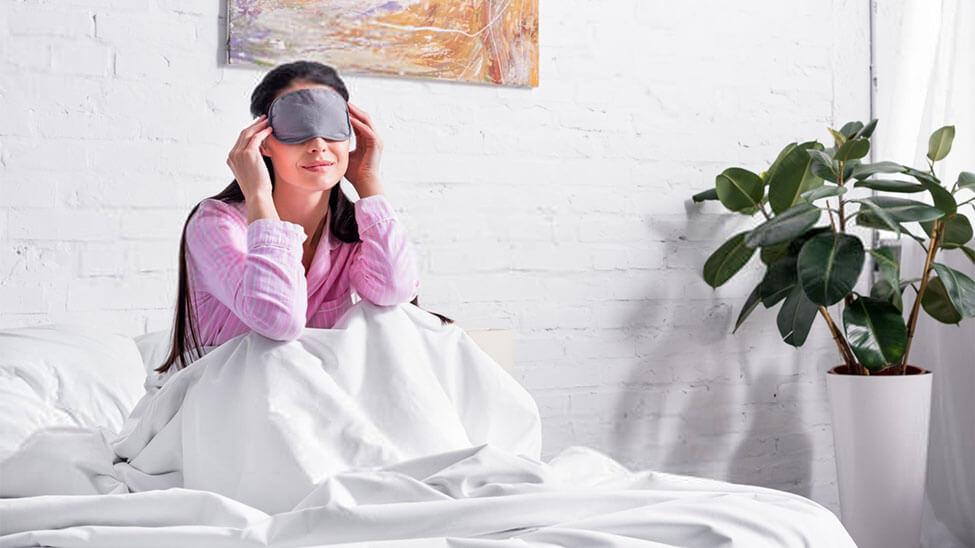 Frau mit Schlafmaske morgens im Bett