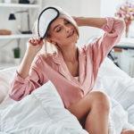Frau nimmt Schlafmaske nach dem Schlafen fröhlich ab