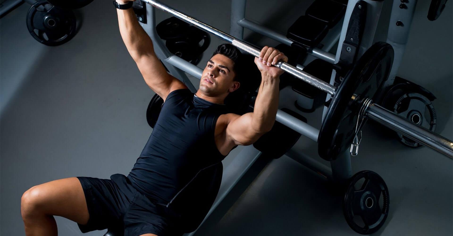 Mann trainiert an Fitnessgerät mit Langhantel