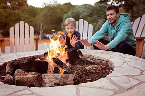 Vater und Sohn wärmen sich an Feuerstelle im Garten