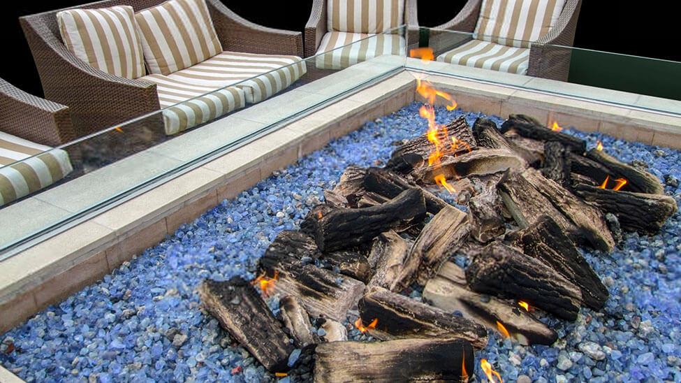 Feuertisch vor Gartenstühlen mit Holz und Glut in der Mitte