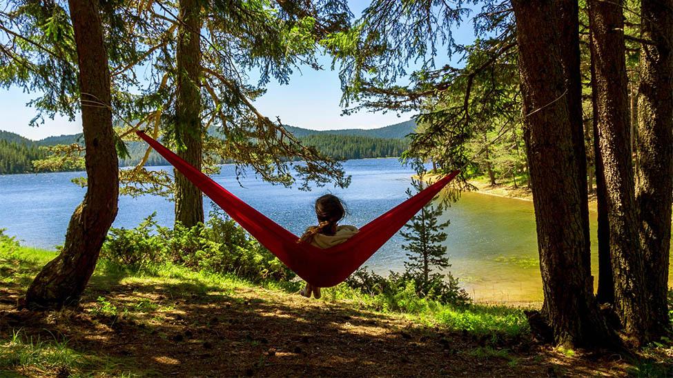Frau in Campinghängematte auf Reisen