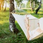 Frau liest Buch in Outdoor Hängematte