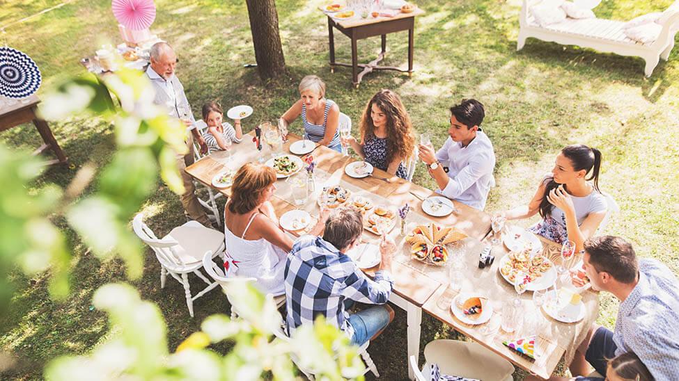 Große Familie feiert Gartenparty mit gedecktem Tisch auf Rasen