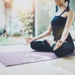 Frau macht Yoga auf Yogamatte