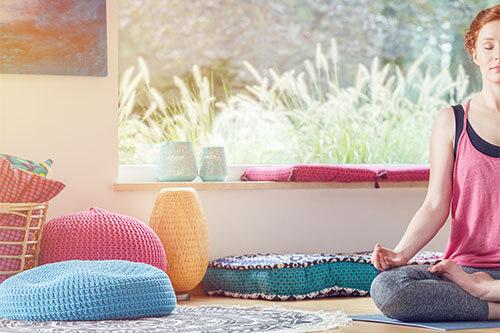 Frau meditiert mit Meditationskissen