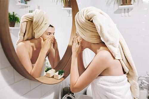 Frau mit Gesichtsmaske vor dem Spiegel im Bad