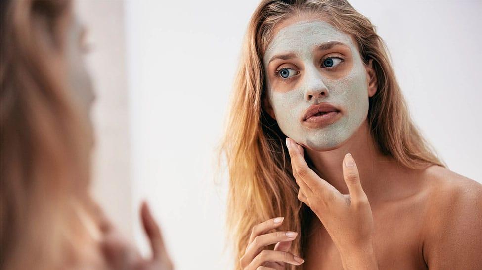 Frau mit Gesichtsmaske aus Creme