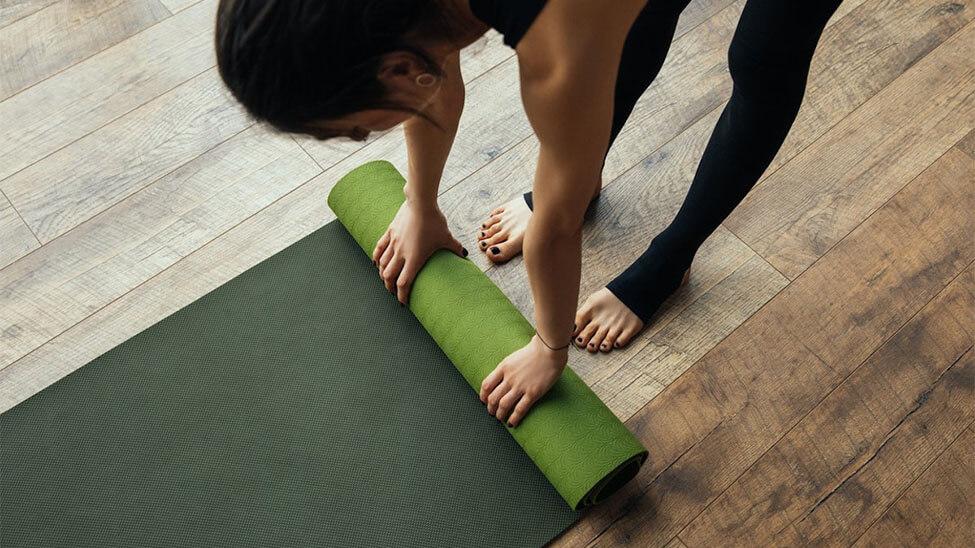 Frau rollt Yogamatte auf