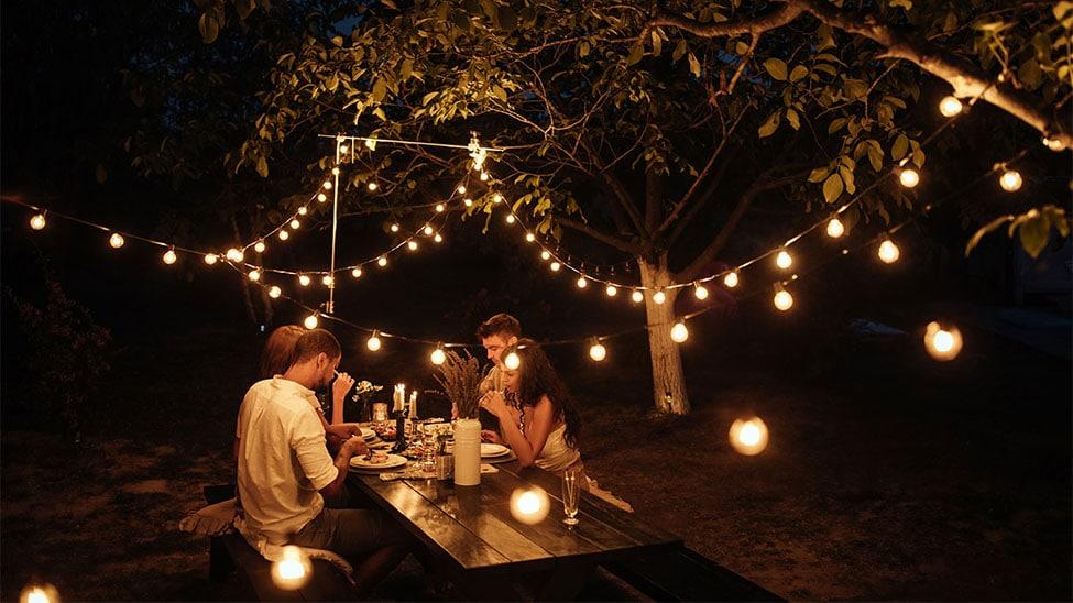 2 Paare im Garten unter Lichterketten