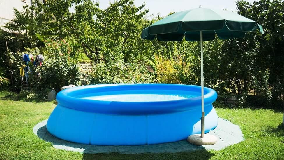 Aufblasbarer Pool neben Sonnenschirm im Garten