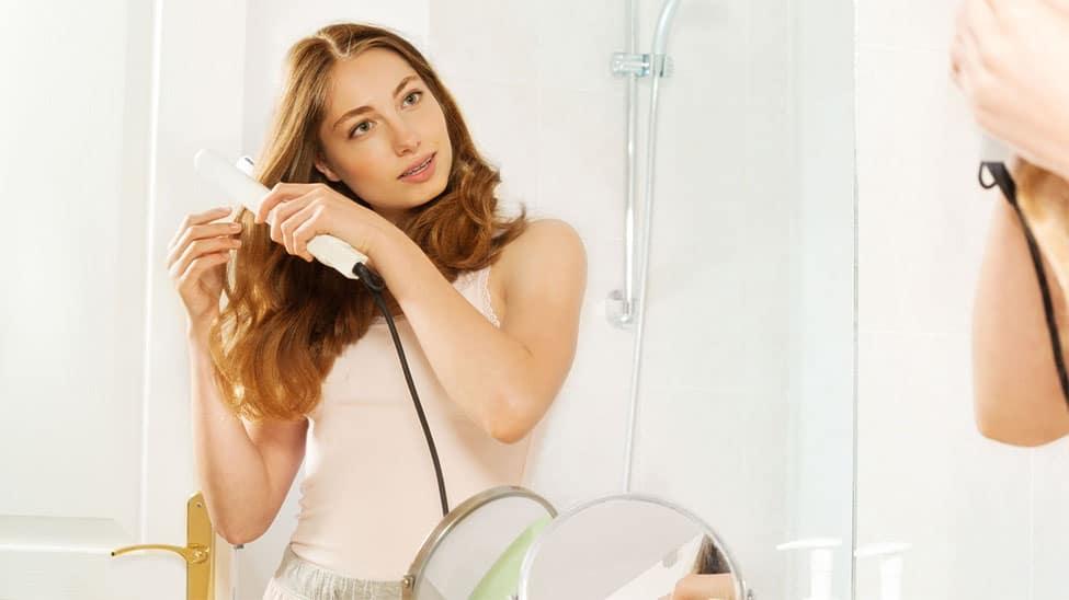 Frau glättet Haare im Badezimmer